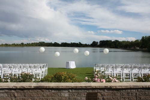 White balloons created a festive background for a wedding ceremony with white garden chairs.