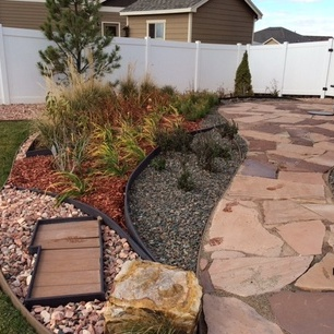 Numerous garden beds in a leaf inspired design surround this flagstone patio and help to soften the stone and add accent color.