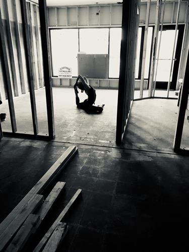 First asana or posture in the studio during the build-out: pigeon pose or raja kapotasana.