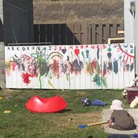 Our backyard fence painted by our Infants and Toddlers.