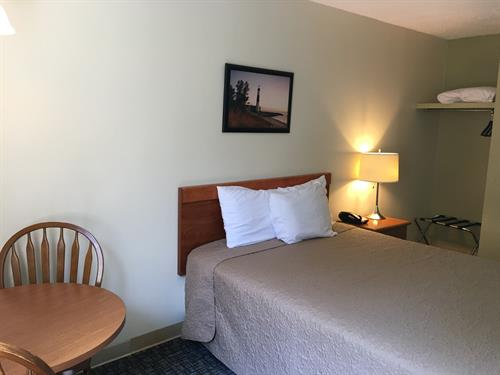Our smaller rooms, One Queen; flat screen TV, refrigerator, coffee and table/ chairs in room.