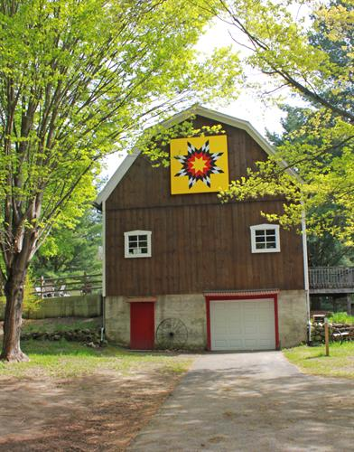North face of barn with 'Blazing Star' Barn Quilt painted by artist, Janice Shelly