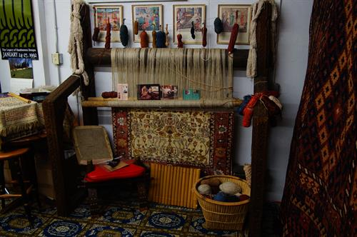 A hand-tied silk oriental rug is on the loom for your enjoyment....a better understanding of just how rugs are woven is made clearer for the observer...