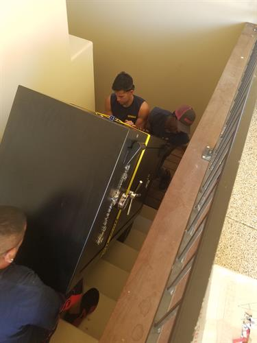 Our hard working crew moving a 400 lbs gun safe into the basement of a new home!
