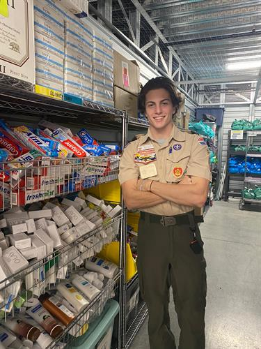 Eagle Scout Tyler with the shelving he built for our hygiene supplies