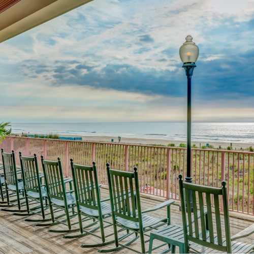Oceanfront Deck with Rocking Chairs | Dunes Manor Hotel Main Building