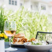 Crispy chicken sandwich and a glass of wine on the waterfront patio