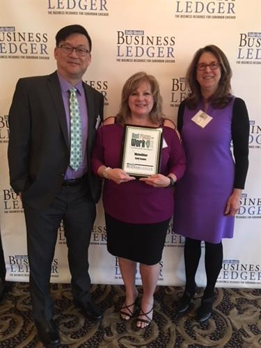 John Hsiao, Paula Gooch, and Judy Mason proudly display the firm's Best Places to Work in Illinois in 2018 Award