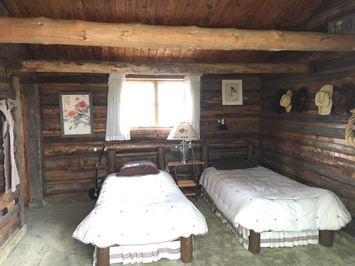 The third bedroom has two twin beds with reading lights, dressers, and authentic Western artifacts that fill the room.