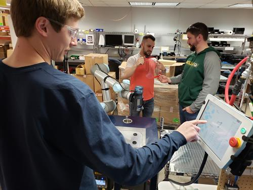 Engineering staff work on PPE equipment for donation using COBOT robot technology