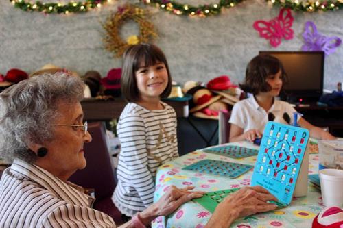 Kindergarten children visit a local senior center for an afternoon of friendship, conversation, and Bingo.