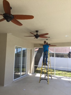 Nick is installing fans on a lanai.