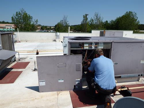 TJ performing a repair on a Roof Top Unit