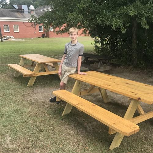 This student is standing by one of four picnic tables that he built as part of his Eagle Scout project.