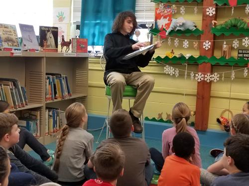 A Trinity Intern and Classroom Assistant reads to a class at St. Michael's School.