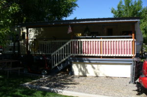 Front View Of Mobile Home Turned Permanent Home With Deck