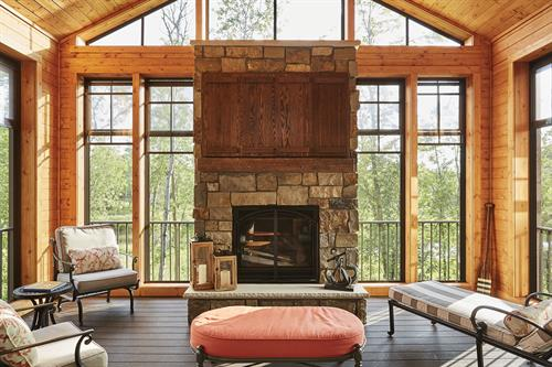 Eze-Breeze 3-season porch with integrated fire place and TV over reclaimed lumber mantel