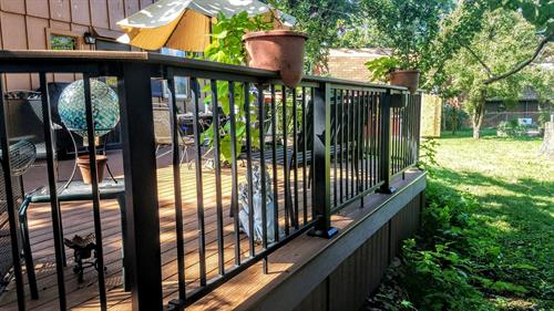 Composite decking and aluminum railing in black and brown/tan profile tones