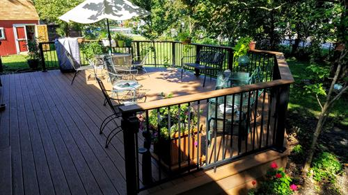 beautiful back yard deck with aluminum handrail and composite drink rail or top rail, drink rail extends over the posts for a continuous