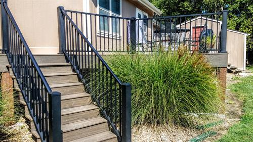 Composite deck with aluminum stair rail and level railing next to a green bush