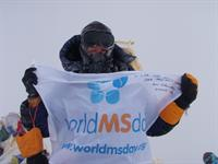 Lori Schneider with World MS Day Flag on summit of Everest, top of the world!