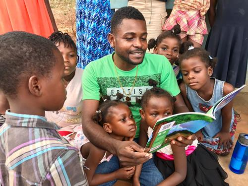Haitian Field Director, Velix Plaisir reading a new book for the Village of Hope Orphanage.