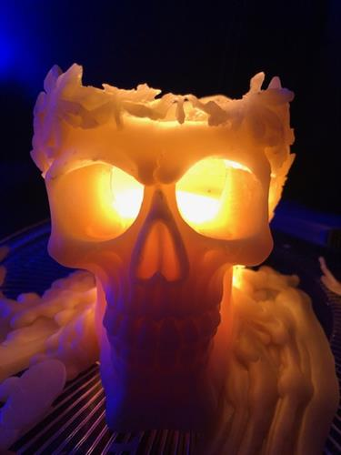 Skull with Leaf Crown Beeswax Candle with candle light flickering through the eyes