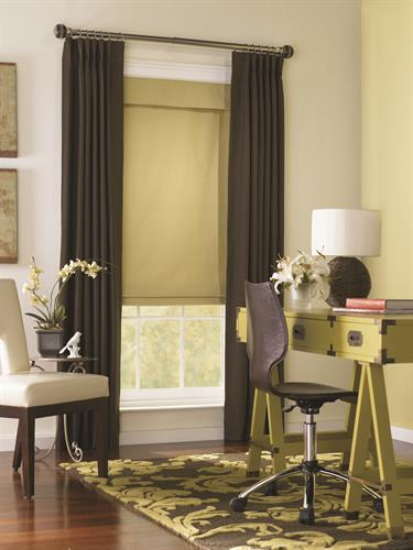 Drapery panels accent a roman shade.