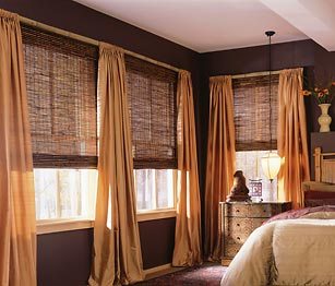 Woven wood shades with puddled drapery panels.