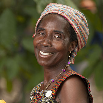 """I am the president of the women's association of Kenadu CARE group. The group is 30 highly motivated women, courageous. Each week we save our money. Before [VSLA], the most I could make in a year was four bags of cocoa beans. But with my CARE money, I bought the fertilizer, when I weighed the cocoa in December I had 752,000 CFA francs and my farm is 2.5 hectares... Do you see how it changed?"