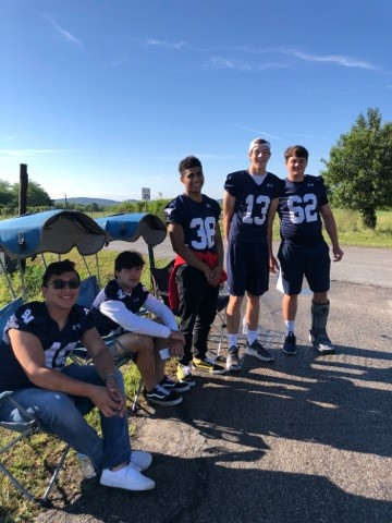 Members of Smithson Valley Varsity football team helping with a water station on the race route.
