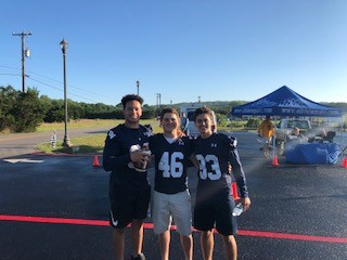 Members of the Smithson Valley Varsity football team helping with the medal distribution for One mile fun run.