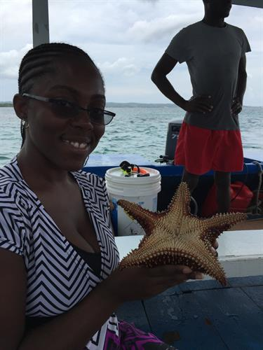 Complimentary Glass Bottom Boat excursion at Sandals Negril - Holding a Star Fish