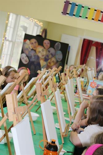 Young artists at La Dee Da working on canvases.