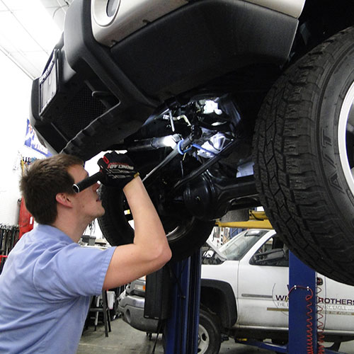 Long Arm Mechanics and Boise Auto Salon owner, Levon Arnold, working on a vehicle