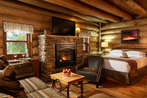 Paul Bunyan log cabin fireplace, living area and queen size bed