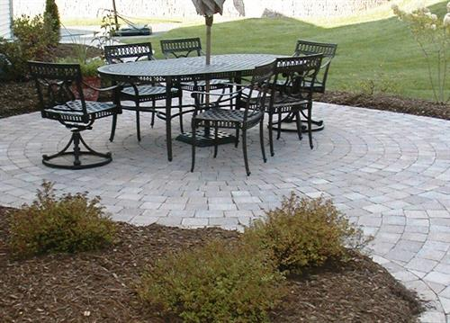 Patios should be sized to allow enough space to get around tables and chairs, but not overwhelm the yard.