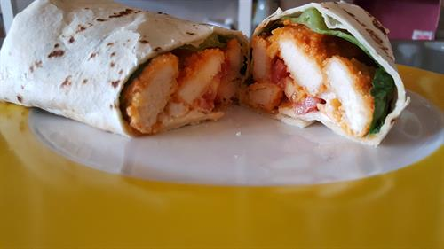 Buffalo Wrap: Sailer's Chicken breast we have breaded and baked by hand and tossed in buffalo sauce, Romaine lettuce, diced tomatoes with ranch dressing and sharp cheddar cheese all wrapped up in tortilla.
