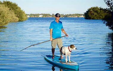 SoBe Surf & Paddle Owner Girard Middleton on touring board with dog Kona