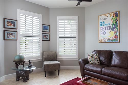 Crisp white Enlightened Style poly-resin shutters accent the inside of this den, while visitors outside your home can also view them peeking through. They're very easily adjusted so you can block the right amount of light at any time of day.