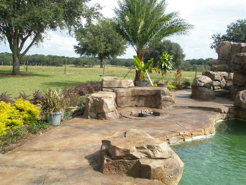 Custom concrete stamped deck surface with boulder fire-pit and seating