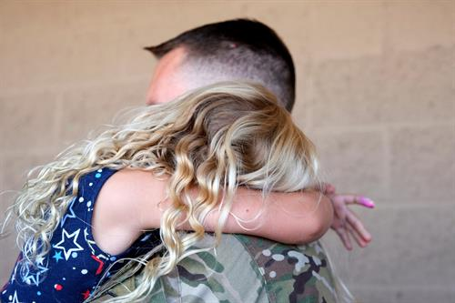 U.S Air Force pararescuemen assigned to the 306th Rescue Squadron at Davis-Monthan Air Force Base, Ariz., hugs his daughter before departing from a deployment. The 306th Rescue Squadron's mission is to rescue isolated personnel or equipment...anytime, anywhere. (U.S. Air Force photo by Andre Trinidad.)