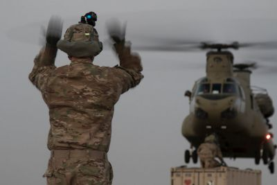 A U.S. Army Soldier, assigned to 2nd Brigade Combat Team, 101st Airborne Division, guides a pilot into place during sling load operations, Aug. 11, 2016 at Camp Buehring, Kuwait. Sling load operations allow U.S. Army Central to move artillery and trucks and shipping containers for mobile operations in the Middle East. U.S. Army photo by Sgt. Brandon Hubbard