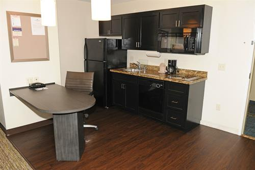 One Bedroom Suite with full kitchen features full-size refrigerator, stove top, microwave, coffee maker, dishwasher, silverware, glassware, plates, pots and pans