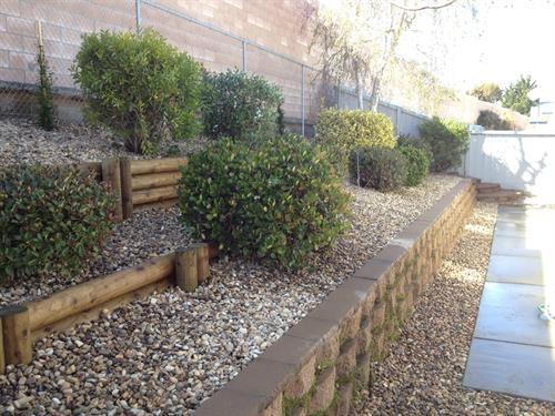 Retaining walls with river rock and finished with some bushes