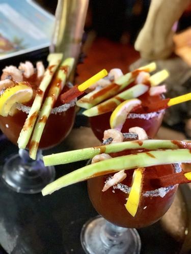 Michelada Ensenada - a twist to the classic Michelada. Garnished with shrimp, cucumber, Chamoy, and tajin