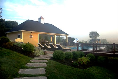 Stone pathway leading to pool deck and pool house.