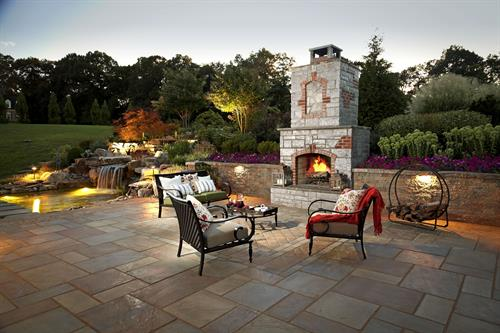 Outdoor fireplace and patio with retaining wall.