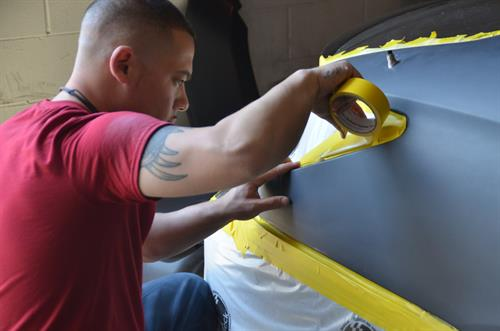 Vehicle being taped to begin the paint process, our paint technicians are meticulous to detail. By taping you are avoiding overspray in areas of the vehicle that don't need to be painted.