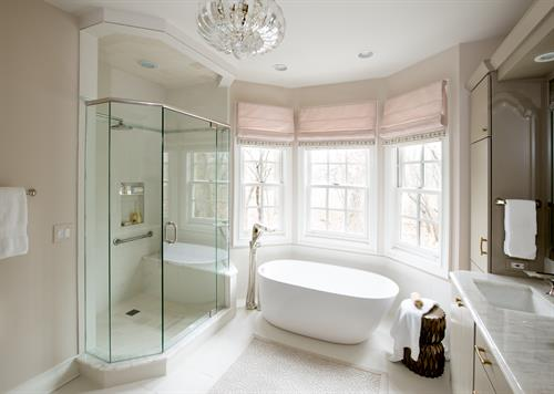 Grey-green cabinets, dusty pink walls and a glamorous chandelier set the scene for a feminine master bath.